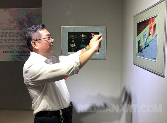 3伊犁州文学艺术界联合会党组书记、副主席甄敬庭兴奋地拍摄展品.JPG